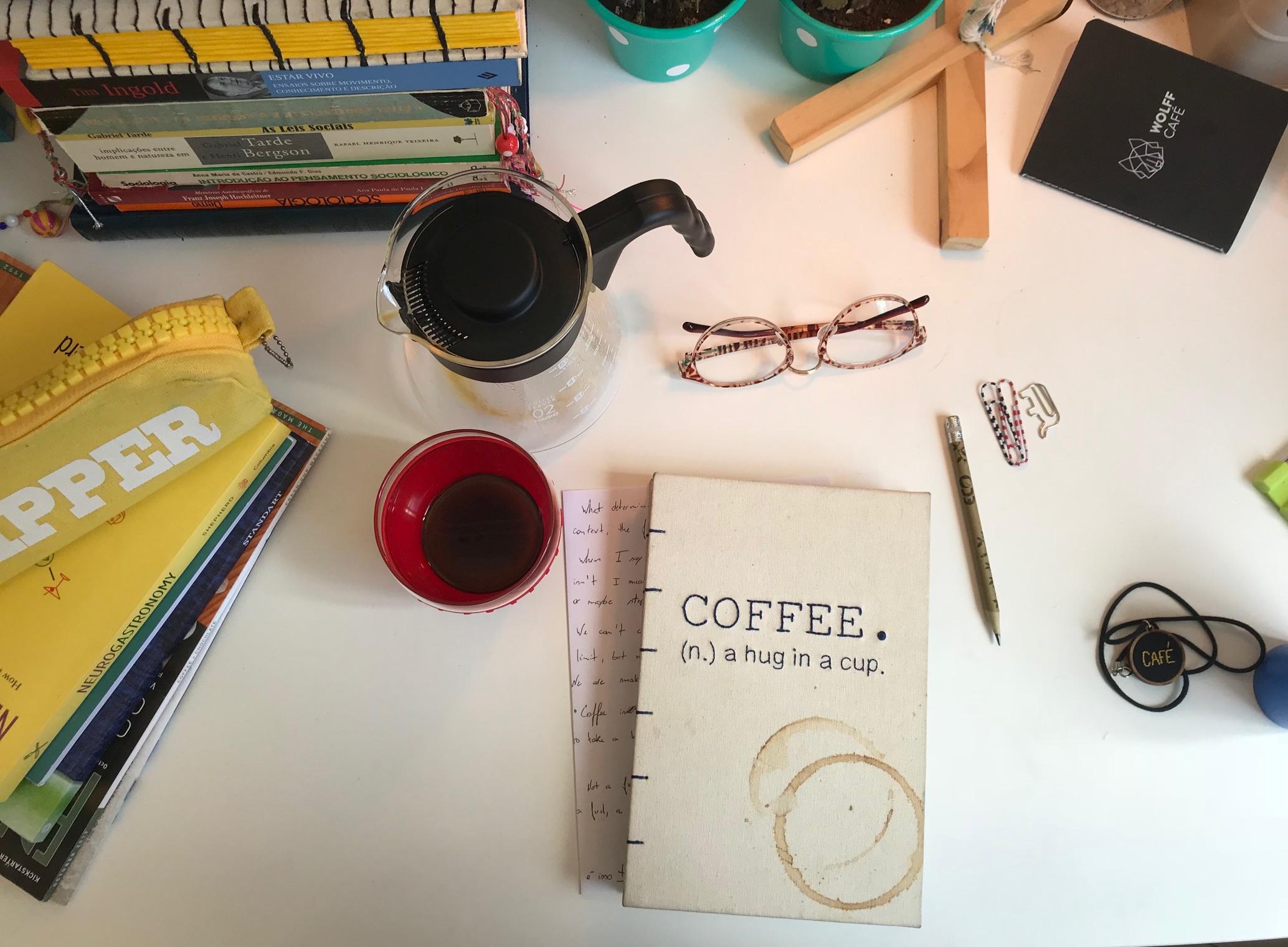Mesa com café, caderno, lápis, luminária, comforty coffee