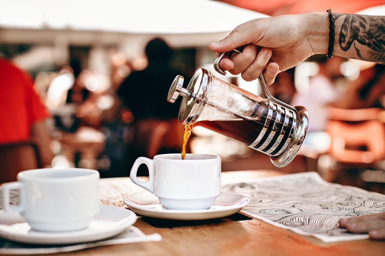 Servindo café de uma prensa francesa, ambiente de cafeteria
